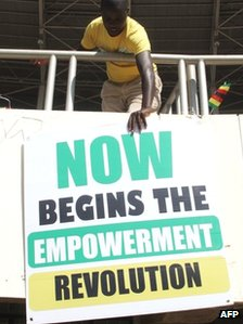 "A supporter of Zimbabwe President Robert Mugabe posts a banner at stadium reading: ""Now begins the empowerment revolution"""