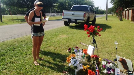 Sarah Harper, Christopher Lane's girlfriend, stands beside a memorial along the road where police say Lane, an Australian baseball player was shot and killed 20 August 2013