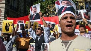 Protesters hold placards and posters of Egypt's ousted President Mohammed Morsi during a protest against army-installed Egyptian government, in front of the Saudi Arabian embassy in Paris on 20 August 2013