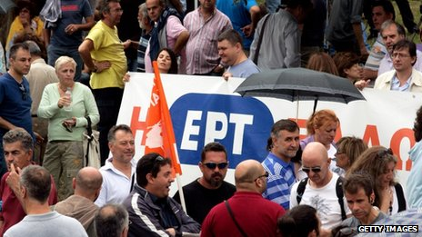 Employees of the Greek public broadcaster ERT hold a banner at the entrance of the corporation's headquarters on 13 June, 2013 in Athens, Greece.