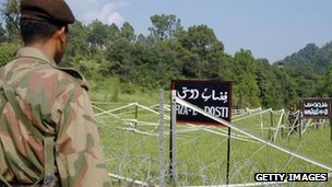 File photo (2006) of a Pakistani soldier watching Indian troops along the Line of Control