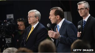 PM Kevin Rudd, left, listens as opposition leader Tony Abbott speaks in Brisbane, 21 August 2013