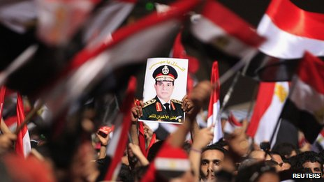 Protesters opposed to President Mohammed Mursi hold a poster featuring the head of Egypt's armed forces General Abdel Fattah al-Sisi in Tahrir Square in Cairo (3 July 2013)