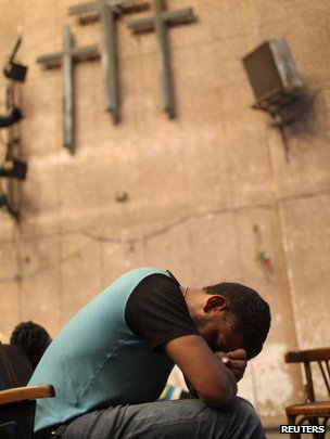 A Coptic Christian sleeps on a chair in a theatre inside Cairo's main Coptic cathedral, following clashes with Muslims (8 April 2013).