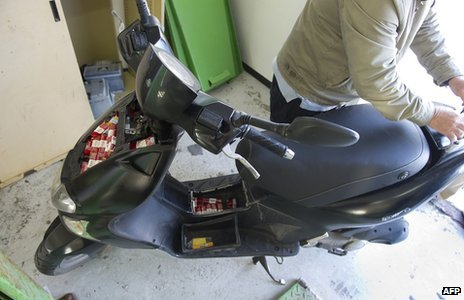 Contraband packs of cigarettes in a motorcycle after it was seized by the Guardia Civil at the border between Spain and Gibraltar. (file photo)