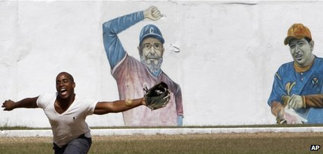 A prisoner plays baseball at the Combinado del Este prison, where a mural of Cuban leader Fidel Castro and Venezuela President Hugo Chavez cover a wall, in Havana, Cuba, Tuesday, 9 April, 2013