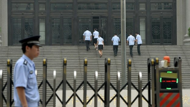 Police stand guard outside the Intermediate People's Court in Jinan