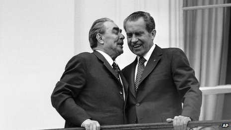 Soviet leader Leonid Brezhnev, left, whispers in the ear of President Richard Nixon as the two leaders stand on a balcony at the White House in Washington 18 June 1973