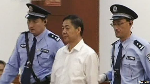 Bo Xilai, is escorted into court by two police officers during his trial in Jinan, Shandong province 22 August 2013, in this still image taken from video