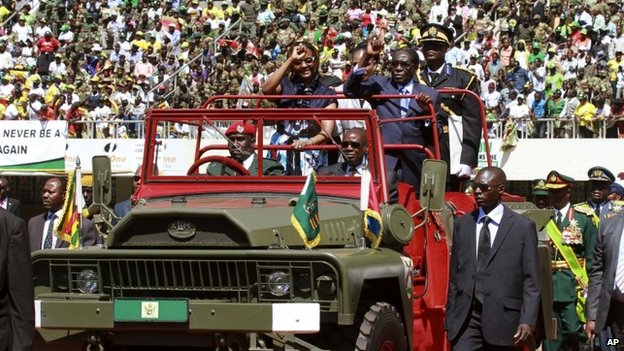 Zimbabwean President Robert Mugabe  and his wife Grace greet the crowd as they arrive for his inauguration in Harare, Thursday 22 August 2013