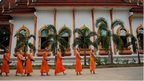 Thai Buddhist monks walk past temple