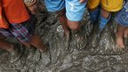 Filipino residents step on muddied streets outside their homes as they wait for local celebrities donating goods to flood affected communities living near the banks of the swollen Laguna lake in Laguna province, southern Philippines on Thursday, 22 August, 2013