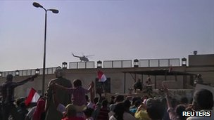Supporters wave as the helicopter carrying Mr Mubarak leaves the prison