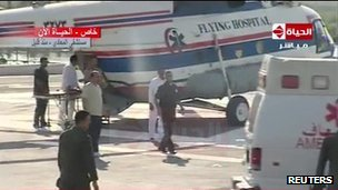 An ambulance transfers Mubarak from the helicopter to a military hospital