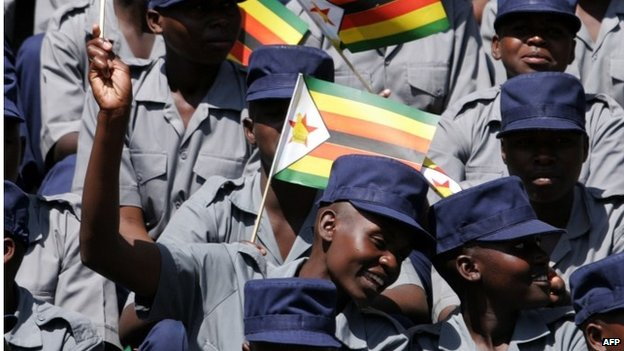 Members of the Zimbabwean Republic police wave flags during the inauguration ceremony and swearing-in of Zimbabwean President Robert Mugabe on 22 August 2013