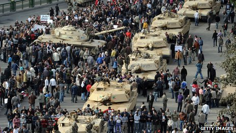 A column of Abrams tanks line the street as Egyptian demonstrators gather in Tahrir Square in Cairo, on 30 January 2011