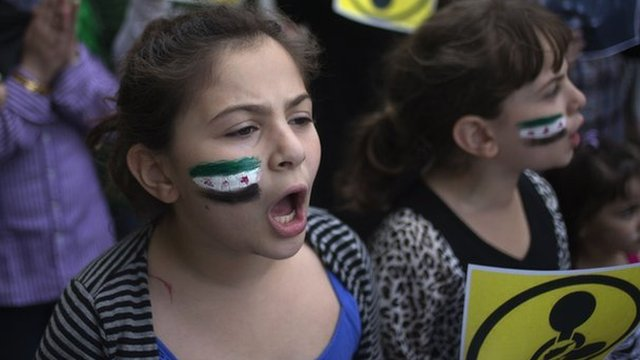 Girl with Syrian flag painted on cheek outside United Nations in New York