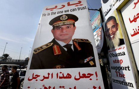 Egyptians walk behind a banner depicting US President Barack Obama, right, and a banner supporting Egyptian Army Chief Gen al-Sisi, in Cairo, August 5, 2013.