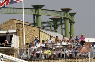 Spectators watch from an apartment outside the ground