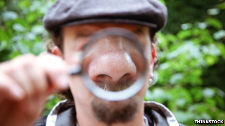 Man holding magnifying glass over his nose