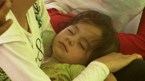 A sleeping child being held in an adult's arms at the Kawargosk refugee camp, August 2013.
