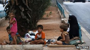 Homeless refugees from Syria rest by the side of a road in the capital Beirut