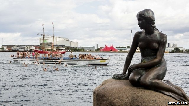 Little Mermaid statue and 100 'mermaids' jumping off boat behind it
