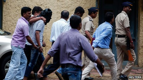 Police escort rape suspect (with his face covered) into court in Mumbai on 24 August 2013