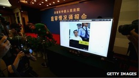 Journalists shoot a screen showing a picture of former police chief Wang Lijun