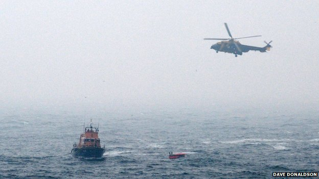 Rescuers approaching a life raft from the crashed helicopter