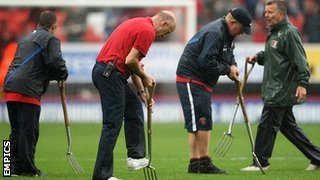 Groundstaff tend to the sodden playing surface at the The Valley
