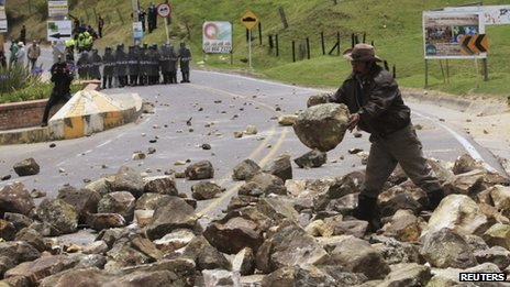 A protester drops a stone on a road in La Calera, near the capital Bogota on 23 August 2013