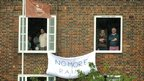 """Residents overlooking the Oval hang a """"no more rain banner"""" from their windows"""