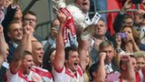 Wigan's Sean O'Loughlin holds the Challenge Cup aloft