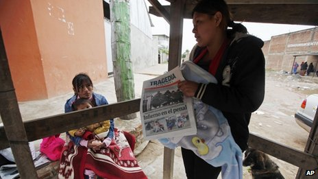 A woman reads a newspaper in front of Palmasola jail on Santa Cruz, Bolivia, on 24 August 2013