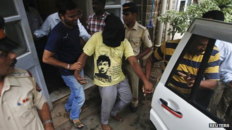 Police officers escort a man (face covered), the third arrested in connection with the gang rape of a photo journalist  in Mumbai