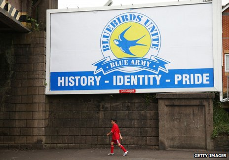 A campaign billboard near the ground, while a fan walks past in the club's red shirt
