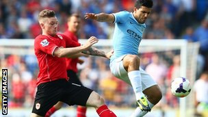 Sergio Aguero of Manchester City controls the ball under pressure from Aron Gunnarsson of Cardiff