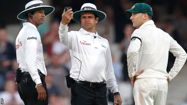 Umpires Aleem Dar and Kumar Dharmasena assess the light meter