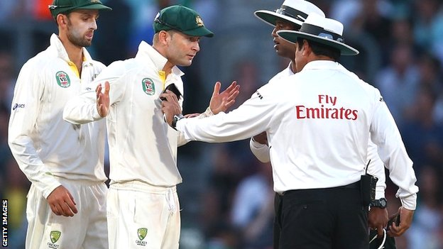 Umpires Aleem Dar and Kumar Dharmasena discuss the light in rather animated fashion with Australia captain Michael Clarke