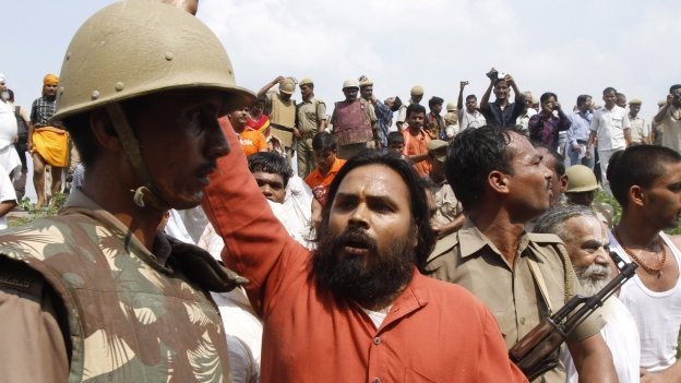 Activists of the Hindu right-winged Vishwa Hindu Parishad, or World Hindu Council (VHP) scuffle with Indian policemen before getting detained at Ayodhya, India, Sunday, Aug. 25, 2013.