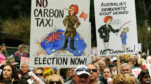 Protesters hold placards as they attend a rally in Sydney on 1 July 2012