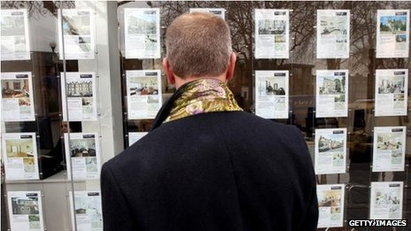 Man looking in estate agent's window