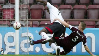 Kevin McHattie slides in to tackle Calvin Zola during the match at Tynecastle