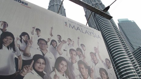 A poster showing Malaysia being a multi-racial country against the Petronas Towers in Kuala Lumpur