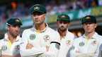 Michael Clarke, who captained Australia's heaviest Ashes series defeat since 1978-79, looks on at the celebrations glumly.