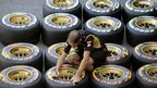 A man marks tyres in pit lane