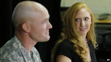 Shannon Carter, right, looks at her husband, US Army Staff Sgt Ty Carter, left, as he talks to reporters, at Joint Base Lewis-McChord in Washington state, on 29 July 2013