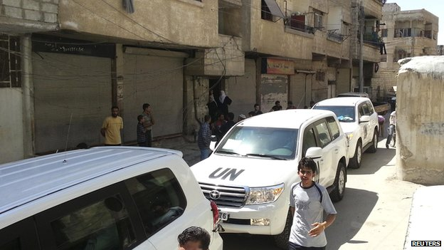 Residents gather around a convoy of UN vehicles carrying a team of UN chemical weapons experts at one of the sites of an alleged poison gas attack in the Damascus suburb of Muadhamiya on 26 August 2013