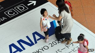 Passengers walking over an ANA logo in Tokyo airport